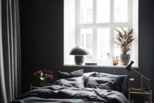 12 a contemporary bedroom with black walls, some bulbs and lamps and a dark bedding set