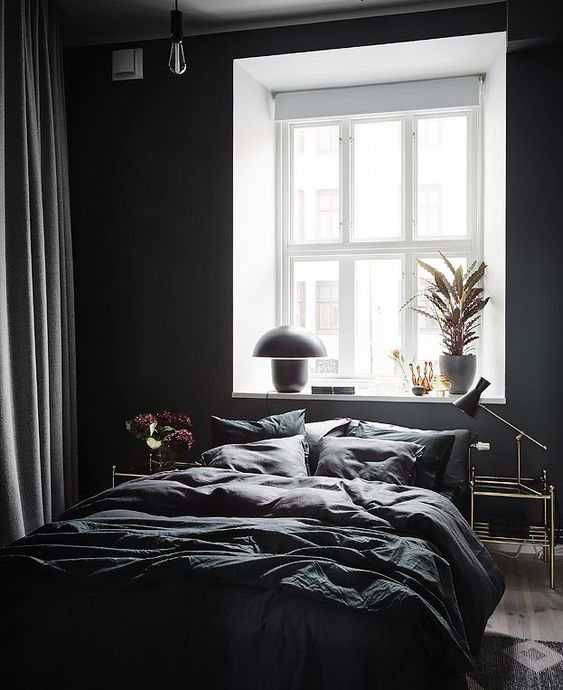 a contemporary bedroom with black walls, some bulbs and lamps and a dark bedding set