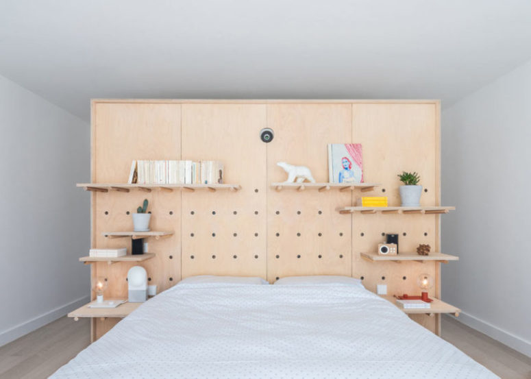 The master bedroom is done with a pegboard headboard for functionality and lots of shelves plus a bed