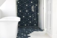 13 a laconic bathroom done with white tiles and navy hexagon tiles with stars that come under the tub