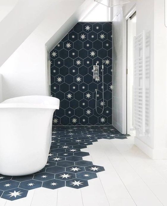 a laconic bathroom done with white tiles and navy hexagon tiles with stars that come under the tub