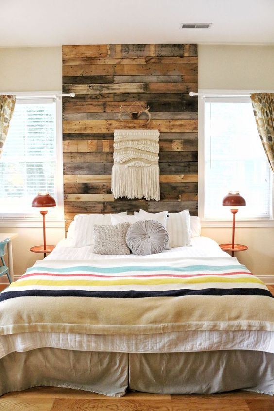 a reclaimed wood headboard coming up to the ceiling is accented with a macrame hanging and antlers for a boho feel