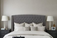 13 an elegant charcoal grey tufted wingback headboard, a crystal chandelier and a leather bench make up a glam modern space