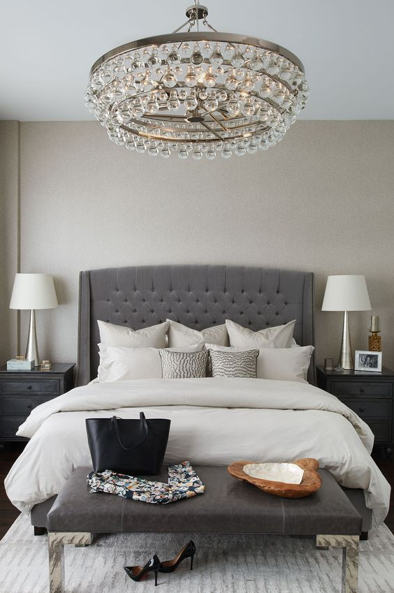 an elegant charcoal grey tufted wingback headboard, a crystal chandelier and a leather bench make up a glam modern space
