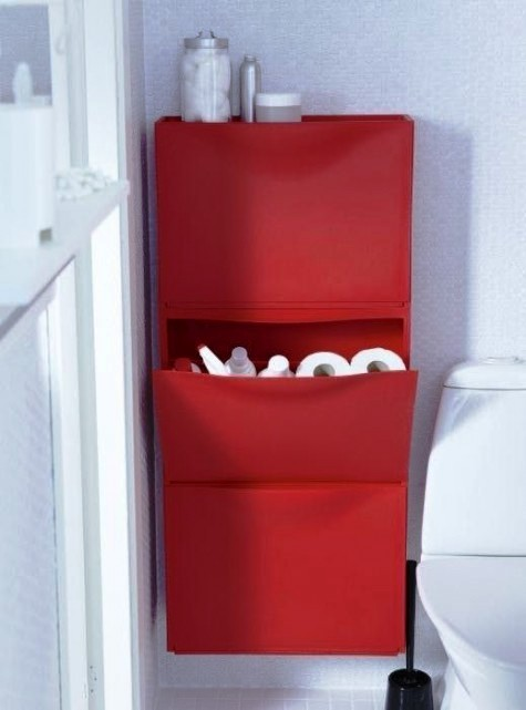 a bright red IKEA Trones piece attached to the wall and used for storing bathroom supplies