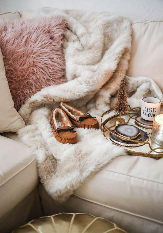 a pink faux fur pillow and a neutral fur blanket are amazign to cozy up in the fall