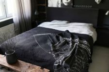 15 a Nordic bedroom with black walls, a chic bedding set, artworks and white touches