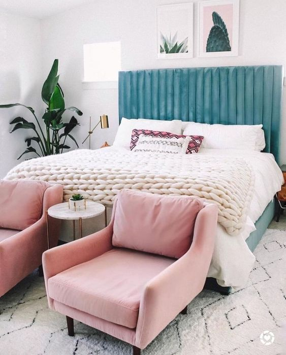 a beautiful blue upholstered headboard is soft and chic, and light pink chairs continue the pastel tone of the space