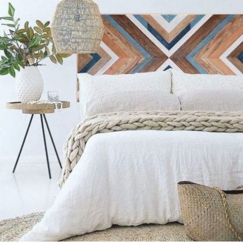 a painted wooden headboard with a chevron pattern, a wicker lampshade and a jute rug for a boho meets rustic feel