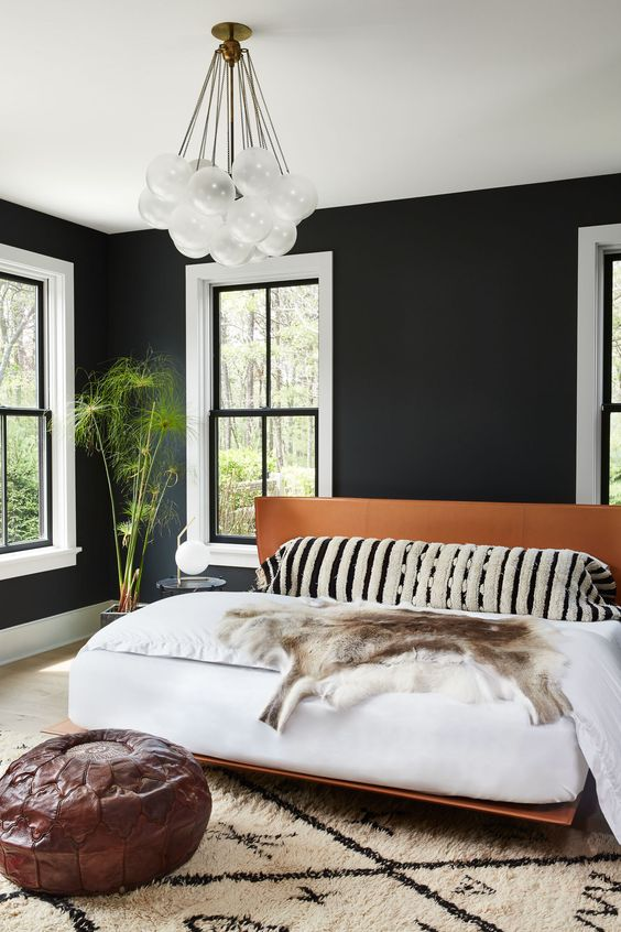 a stylish mid-century modern bedroom with black walls, a creative chandelier, a leather bed and white windows