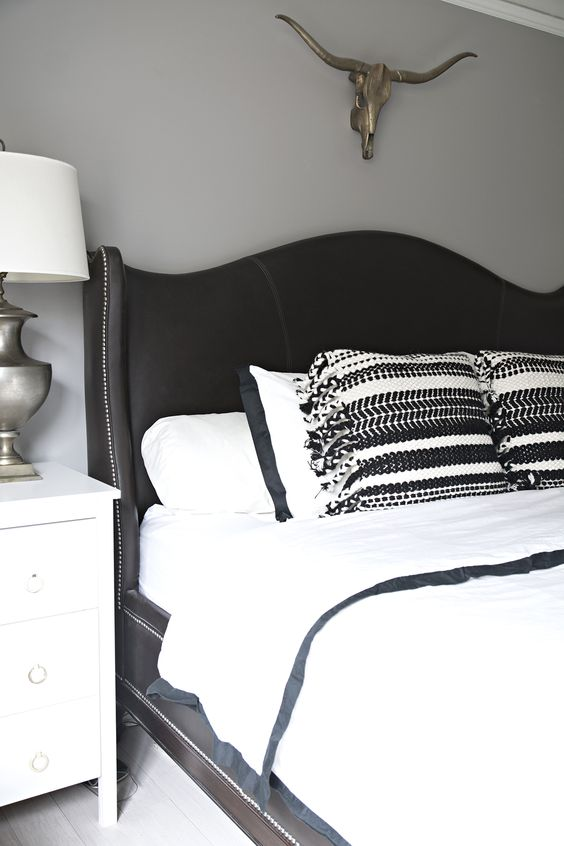 a black curved wingback headboard with decorative nail trim is a chic vintage-inspired idea