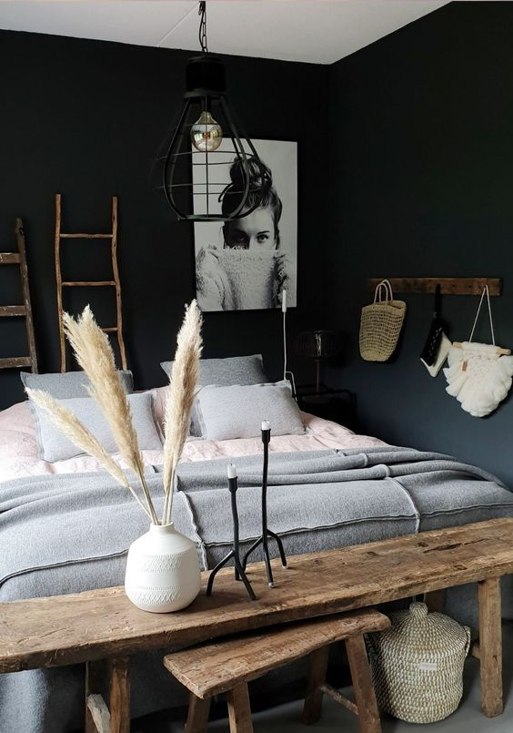 a chic bedroom with black walls, grey and white touches, wood to warm up the space
