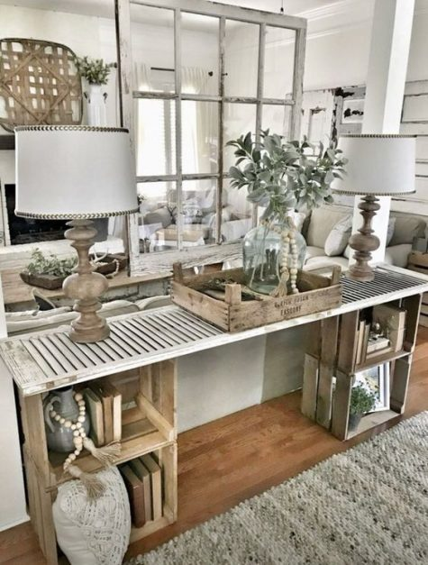 a farmhouse console table made of wooden crates and a shutter looks very rustic and relaxed