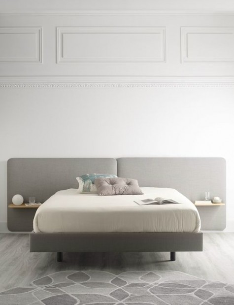 a modern grey upholstered headboard with floating nightstands attached is a laconic and stylish solution