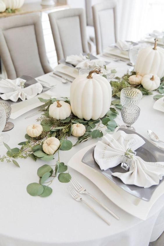 spruce up the tablescape with neutral pumpkins of various sizes and some fresh greenery