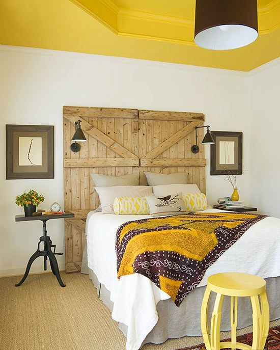a barn door used as a headboard in this bright bedroom features lamps and add a cozy rustic touch