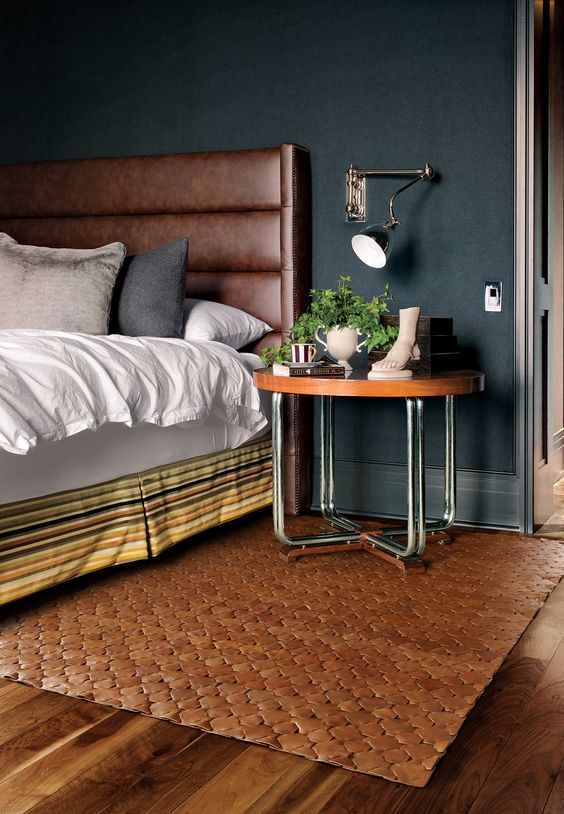 a brown leather padded wingback headboard, a matching rug and a wooden top nightstand warm up the moody bedroom