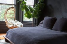 18 a welcoming bedroom with black walls, potted greenery, a black beddign set and a hanging chair