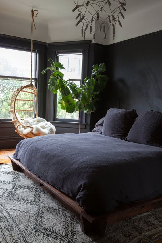 a welcoming bedroom with black walls, potted greenery, a black beddign set and a hanging chair