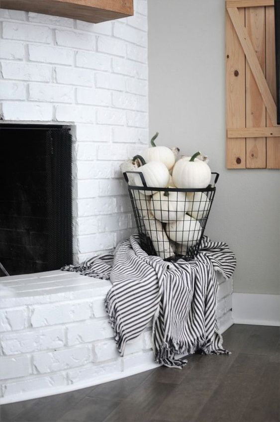 a wire basket filled with white pumpkins and with a black and white blanket will glam up your space