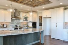 18 ceiling lights combined with elegant chandeliers over the kitchen island to get enough light
