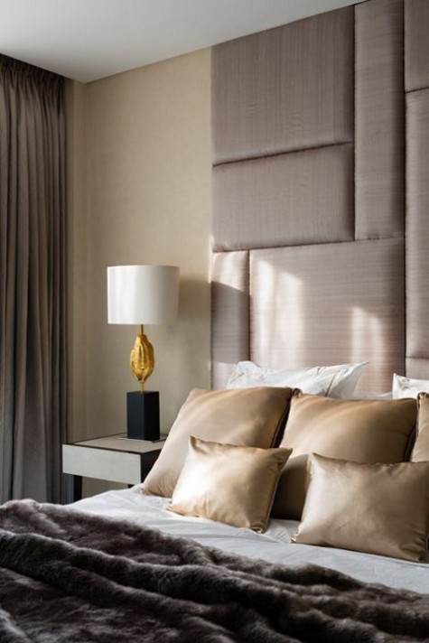 a beige padded upholstered headboard with a geometric pattern comes up to the ceiling and makes an elegant statement