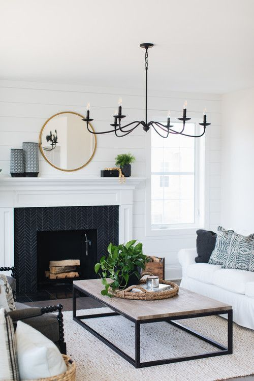 a black chanddelier imitating old candle ones contrasts the neutral space and adds drama