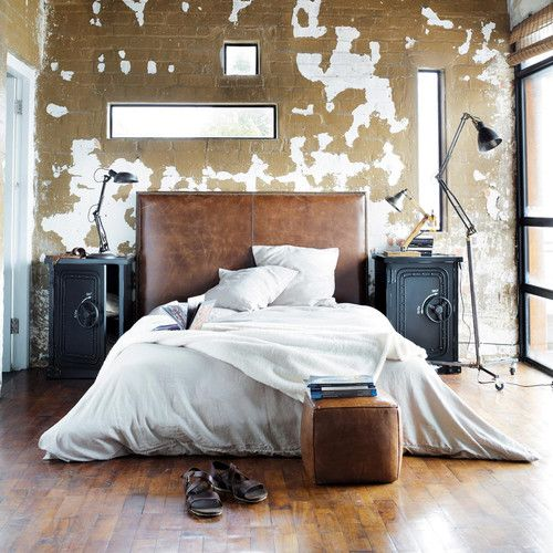 a brown leather sleek headboard and a matching square pouf are a base for an industrial bedroom
