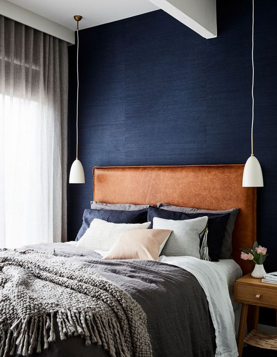 a brown leather upholstered headboard is a warming up touch to the welcoming bedroom done in grey and navy