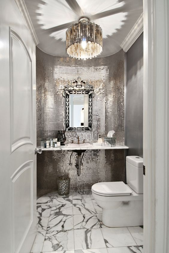 a glam mudroom with shiny reflective tiles, a marble floor and a refined frame mirror