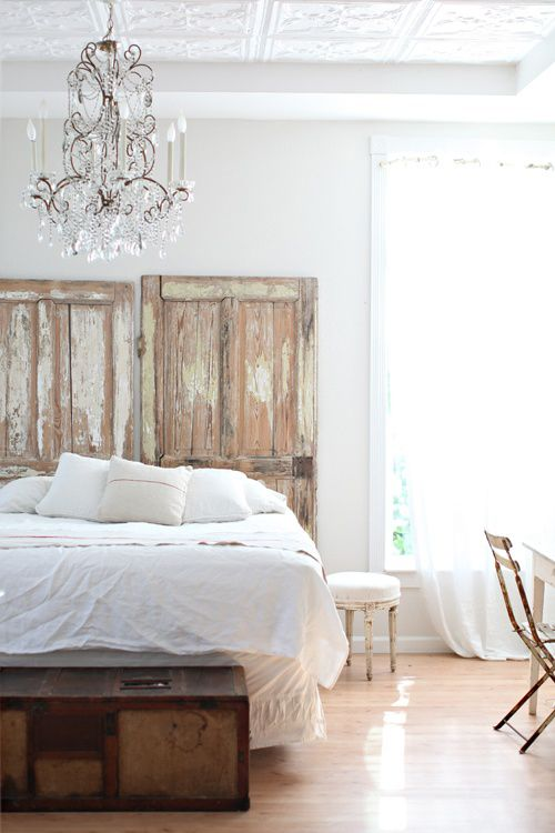 a light filled and airy bedroom with a crystal chandelier, shabby chic doors looks very refined and elegant