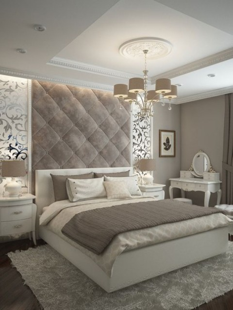 a refined taupe velvet headboard with padding comes up to the refined ceiling and adds a chic statement to the space