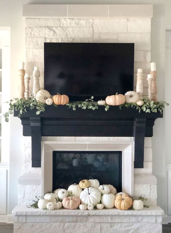 a fireplace decorated with muted and neutral pumpkins, foliage and candles in elegant wooden candleholders