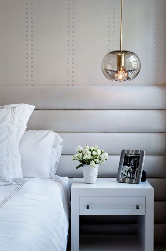 a glass pendant lamp with an eye-catchy shape and gold touches spruces up a neutral bedroom