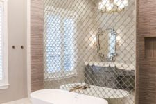 21 a wall done with reflective Moroccan tiles separates the bathtub from the rest of the space and accents it