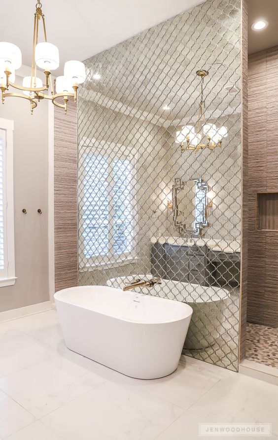 a wall done with reflective Moroccan tiles separates the bathtub from the rest of the space and accents it