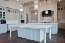 21 ceiling lights and original pendant lamps modernize the farmhouse kitchen done in white