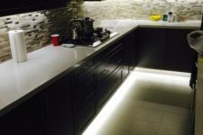 22 a dark kitchen featuring under the cabinet lights and over the countertop lights as ambient lighting