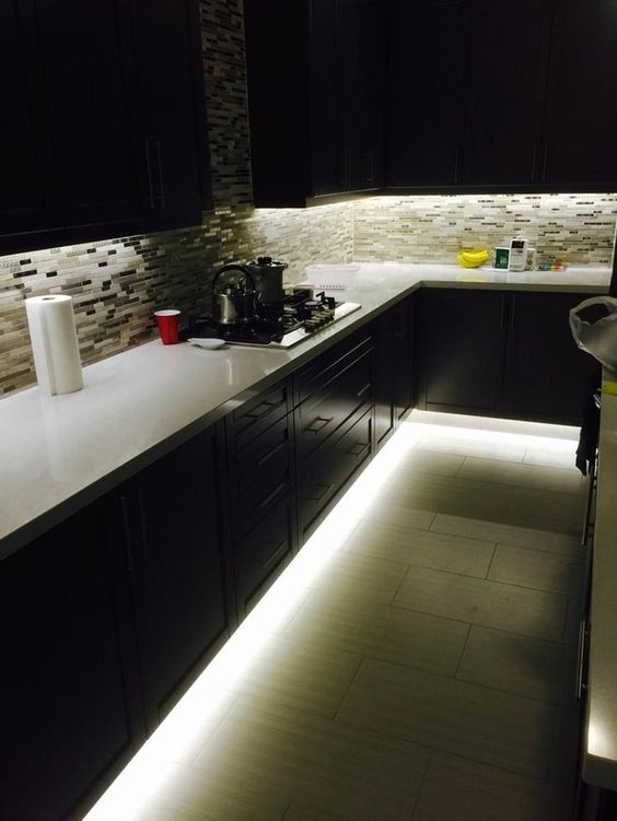 a dark kitchen featuring under the cabinet lights and over the countertop lights as ambient lighting