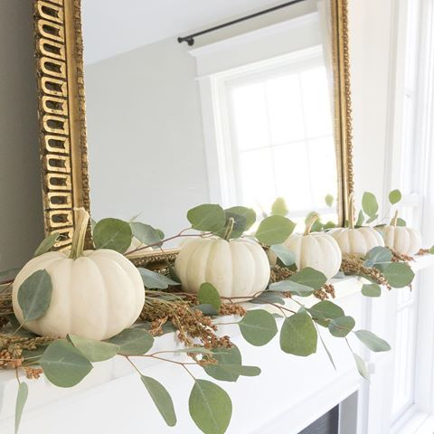 a fall mantel dcorated with white pumpkins, eucalyptus and with a statement gold ramed mirror