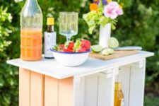 22 a pastel outdoor bar made of crates painted in pastel shades and with a wooden tabletop