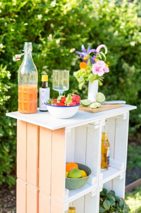 a pastel outdoor bar made of crates painted in pastel shades and with a wooden tabletop