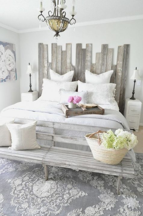 a shabby chic greyish headboard made of planks of different height for a nonchalant feel in the space