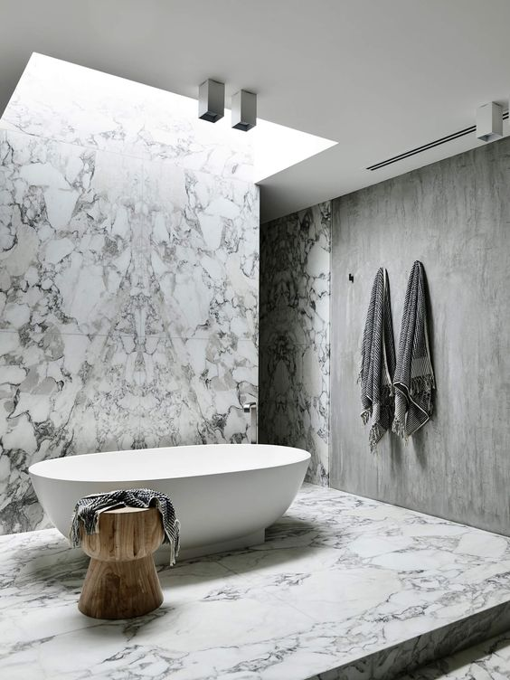 a skylight plus some additional lights on the ceiling make an accent on the tub and bring much light to it