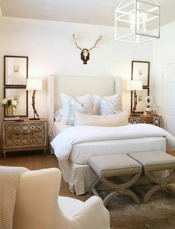 a soft creamy upholstered wingback headboard and matching refined stools for a bold elcectic bedroom