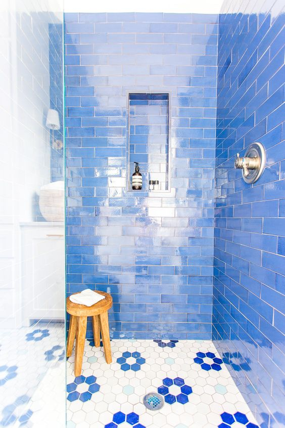 bright blue tiles and hex ones with blue floral accents that highlight the color of the walls