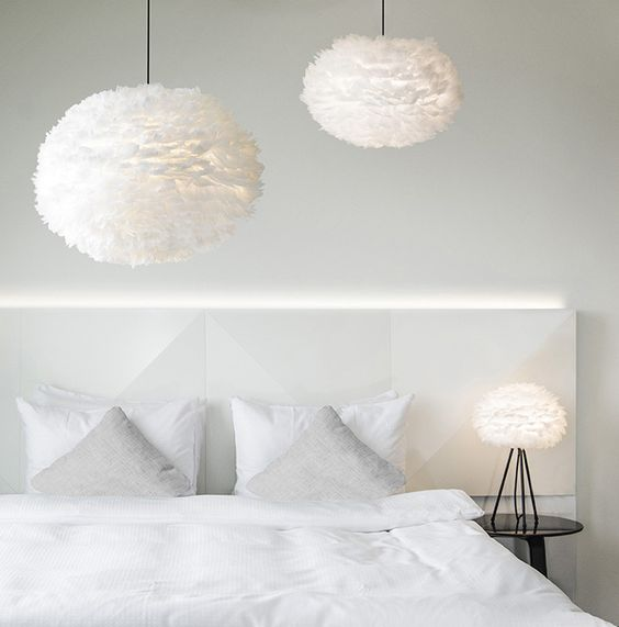 large fluffy feather pendant lamps and an echoing table one create an airy feeling in the bedroom