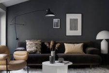 23 a black wall sconce matches the style and colors of this living room providing some cozy light