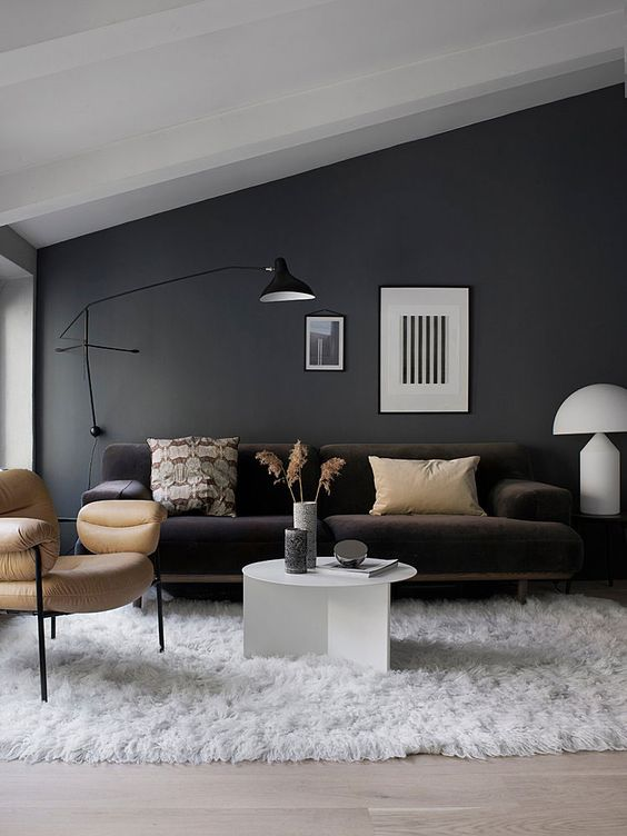 a black wall sconce matches the style and colors of this living room providing some cozy light