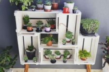 23 a simple and chic garden made of crates and wooden legs is a cute idea of an open storage unit